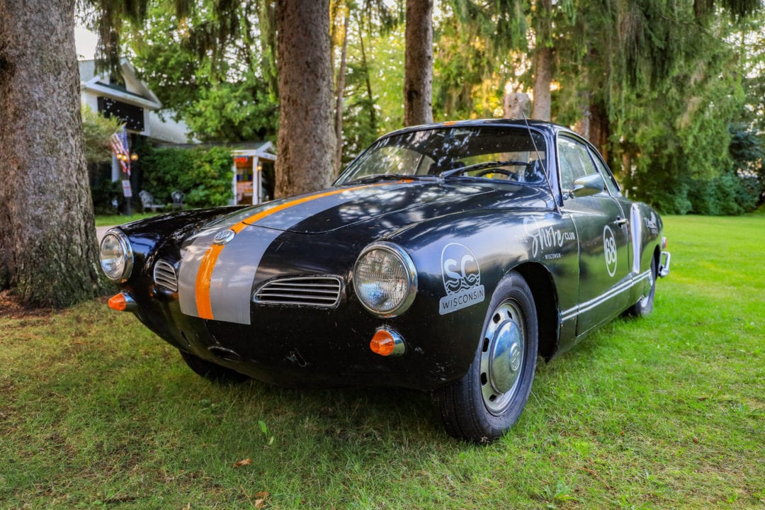 A black vintage sports car with gray and orange racing stripes is parked on a lawn.