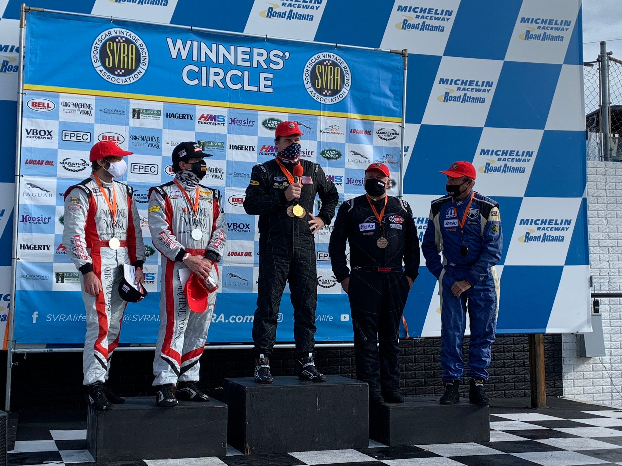 Ford CEO Jim Farley, center, takes first place in the endurance race at the Road Atlanta Grand Prix on Nov. 22. He stands alone on the podium because he raced solo while the other teams each raced the course with two drivers.